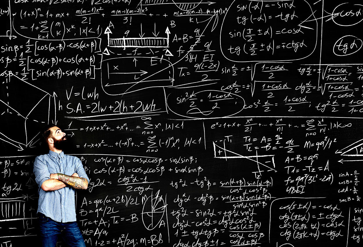 guy in front of a chalkboard filled with math equations
