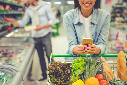 shopping cart with fresh produce pushed by lady texting