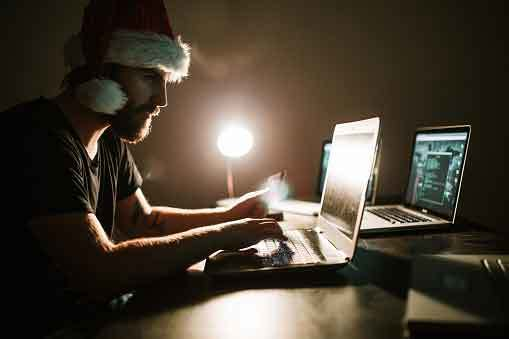 man in santa hat hacking computers