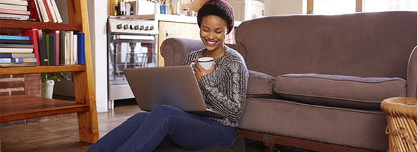 young woman drinking coffee while looking at her laptop