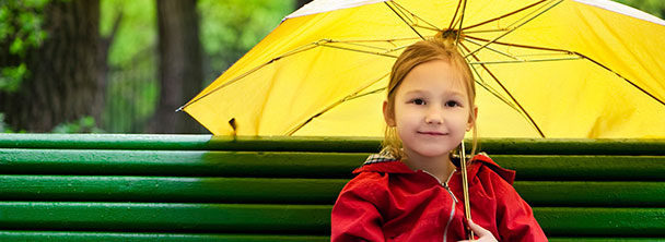 young girl seated on a park bench holding a yellow umbrella
