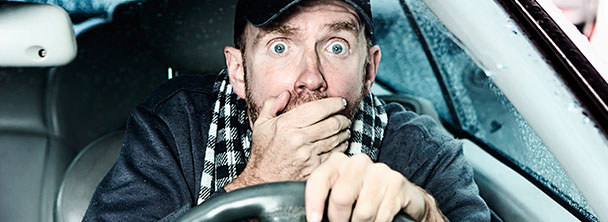 surprised man with his hand over his mouth looking out windshield