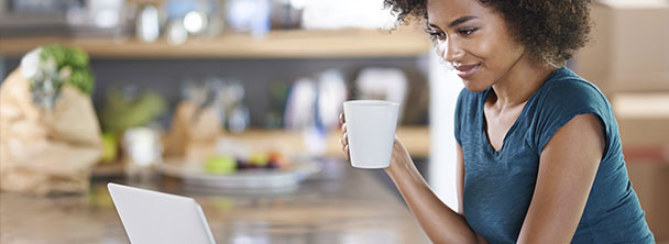 young woman in her kitchen drinking coffee and looking at her laptop