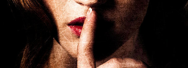 woman with her finger to her lips as if to say shhh