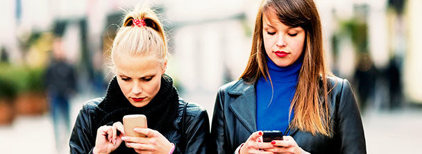 two women standing side by side texting