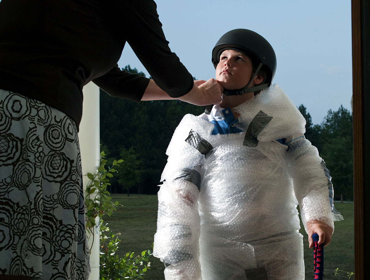 mom at front door strapping helmet on young boy who has his arms, legs, and body wrapped in bubble wrap