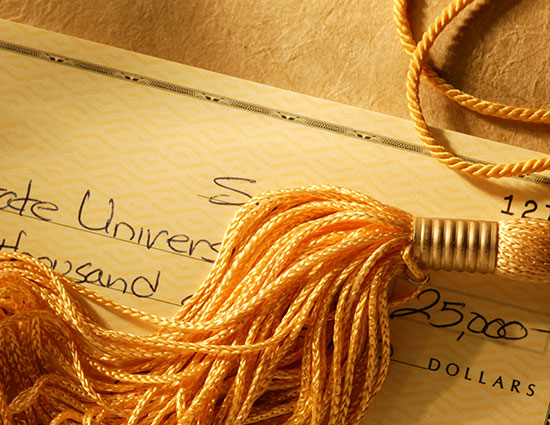 $25,000 personal check made out to a university with a graduation tassle lying on top of it
