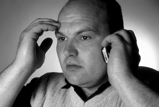 a concerned looking man with his cell phone up to his ear and his other hand on his forehead