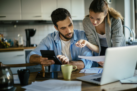 couple with bills, calculator, computer, and coffee in kitchen