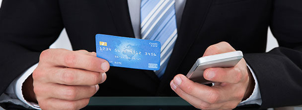 man in a suit and tie holding his phone and a credit card