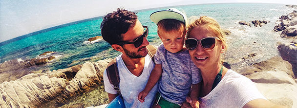 couple with toddler taking selfie at the beach