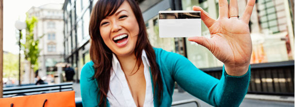young woman laughing and holding up credit card