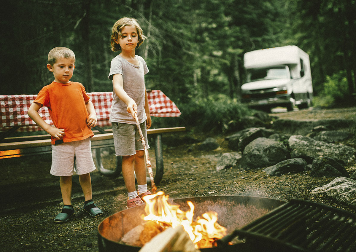 two young boys standing between a picnic table and a fire pit with the older boy poking the fire with a long stick