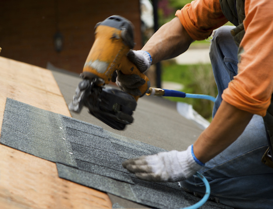 a roofer installing shingles with an air gun