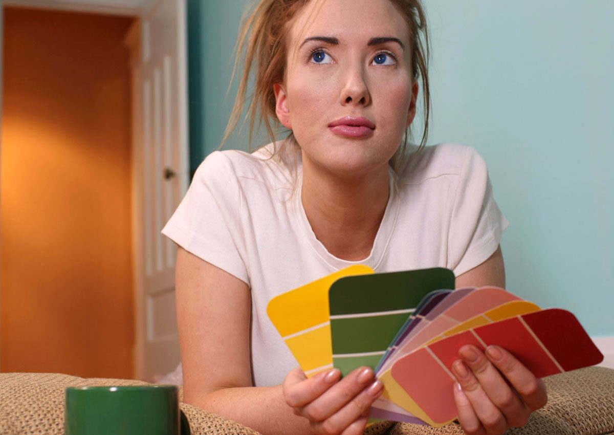 young woman deliberating over paint colors