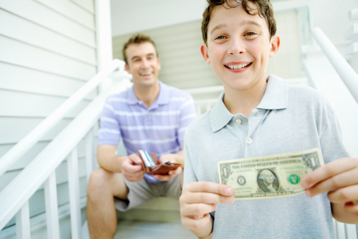smiling dad with an open wallet and smiling 8 year old boy holding up a dollar bill