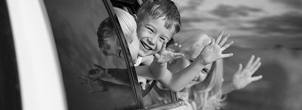three young kids waving from an open car window