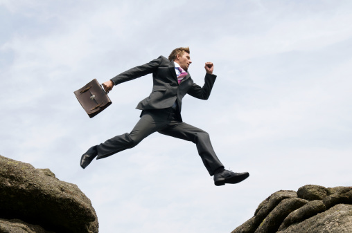man in a suit with a briefcase leaping across a crevice