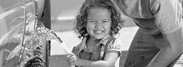 smiling little girl spraying a car with a hose