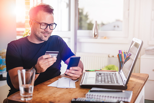 smiling man putting credit card info into his cell phone