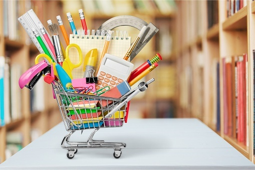 mini shopping cart full of pencils, pens, note pads, paperclips, scissors, and other school supplies