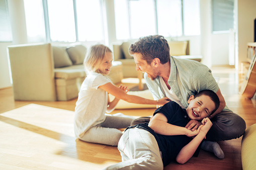 dad in the floor wrestling with grade school age son and daughter