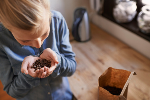 young girl smelling a handful of coffee beans