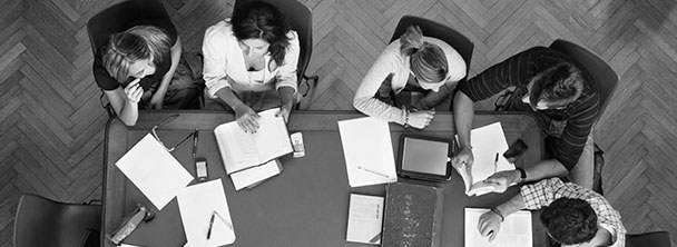 overhead view of five students studying around a table in the library
