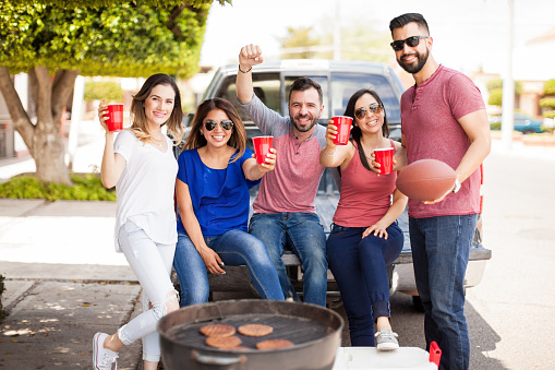 five people sitting on and around the tailgate of a pickup with burgers on the grill and a football in hand
