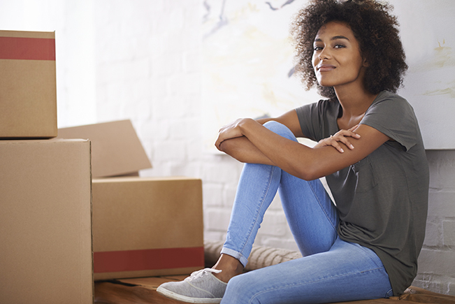woman seated near packed moving boxes