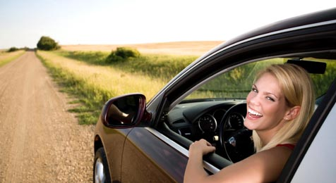 smiling young woman driving car on gravel road